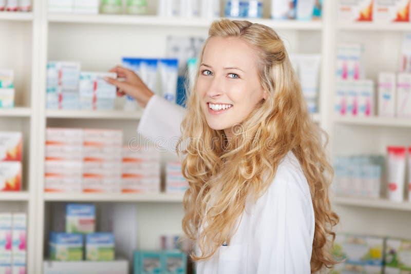 Θηλυκός φαρμακοποιός που παίρνει την ιατρική από το ράφι στοκ φωτογραφία