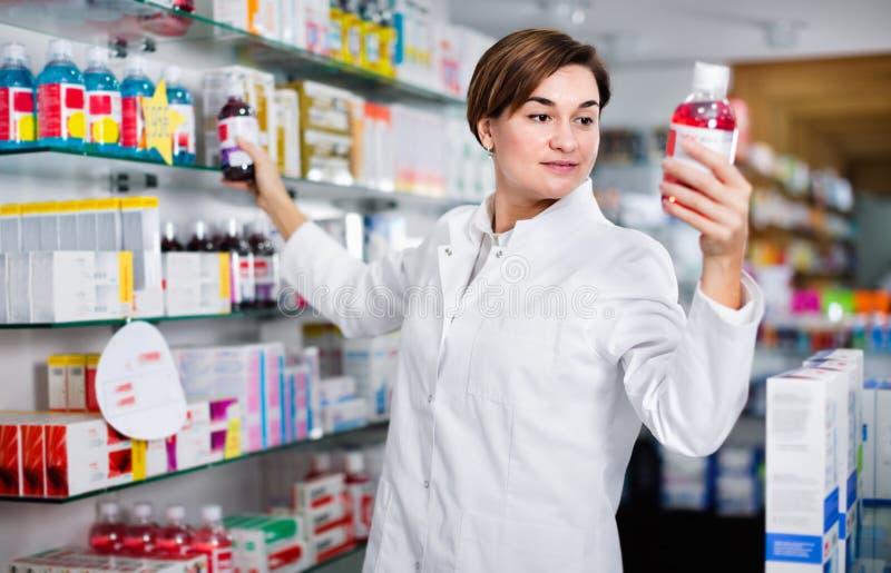 Θηλυκός φαρμακοποιός που προτείνει τα χρήσιμα προϊόντα προσοχής σωμάτων στοκ εικόνα με δικαίωμα ελεύθερης χρήσης