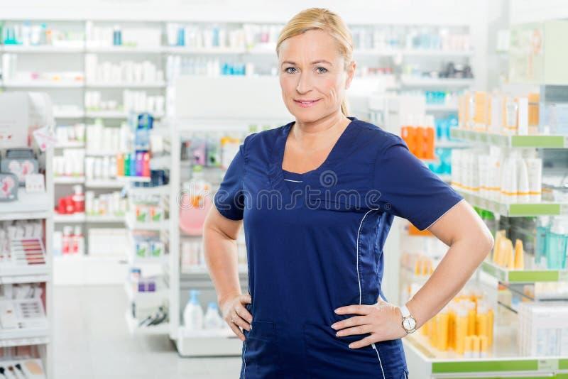 Θηλυκός φαρμακοποιός που στέκεται με τα χέρια στο ισχίο στο φαρμακείο στοκ φωτογραφία
