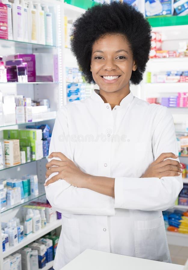 Θηλυκός φαρμακοποιός που χαμογελά στεμένος τα όπλα που διασχίζονται στοκ φωτογραφία με δικαίωμα ελεύθερης χρήσης