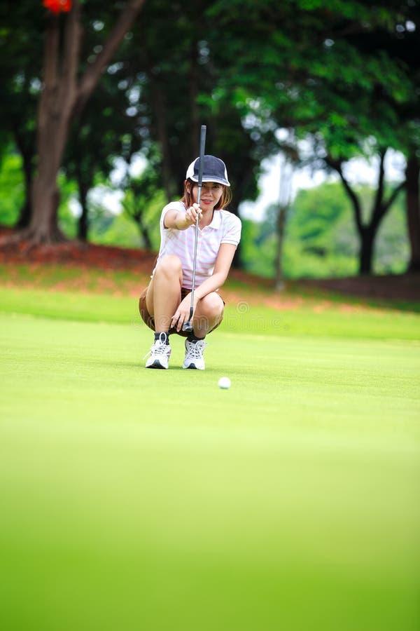 Θηλυκός φορέας γκολφ με το putter που κάθεται οκλαδόν για να αναλύσει το πράσινο στοκ φωτογραφία