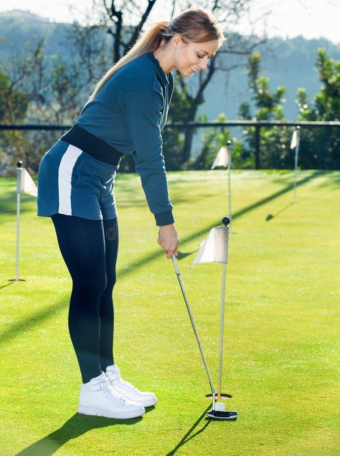 Θηλυκός φορέας γκολφ που παίρνει έτοιμος να χτυπήσει τη σφαίρα στοκ φωτογραφία με δικαίωμα ελεύθερης χρήσης