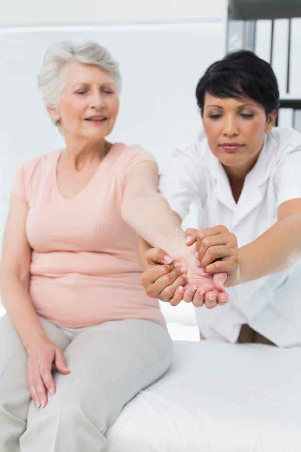 Θηλυκός φυσιοθεραπευτής που εξετάζει ένα ανώτερο χέρι ασθενών στοκ εικόνες