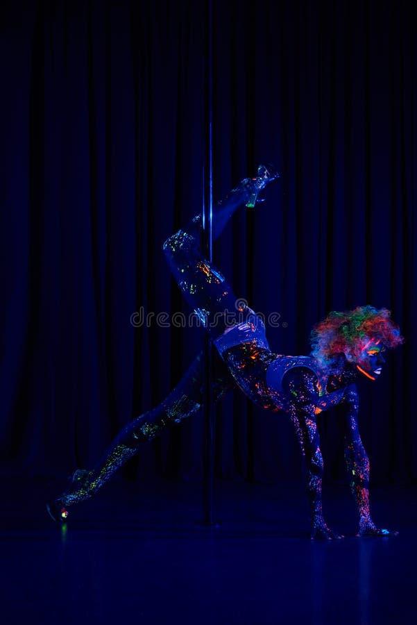 Θηλυκός χορευτής πόλων φωτεινά χρώμα νέου κάτω από την υπεριώδη ακτίνα στοκ εικόνες με δικαίωμα ελεύθερης χρήσης