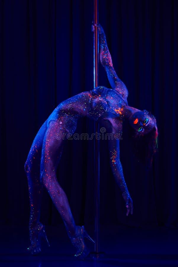 Θηλυκός χορευτής πόλων φωτεινά χρώμα νέου κάτω από την υπεριώδη ακτίνα στοκ εικόνες