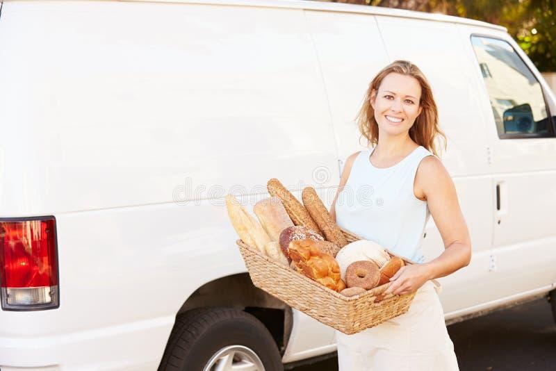 Θηλυκός Baker που παραδίδει το ψωμί που στέκεται μπροστά από το φορτηγό στοκ εικόνα με δικαίωμα ελεύθερης χρήσης