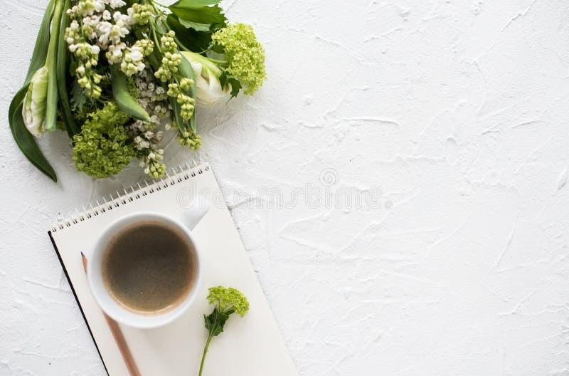 Θηλυκός flatlay με τα λουλούδια και ccoffee άσπρο tabletop στοκ φωτογραφίες