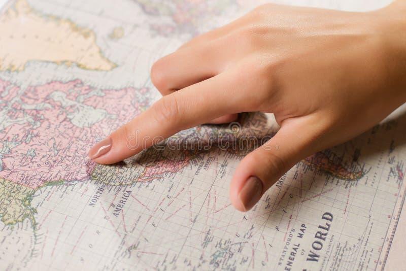 Θηλυκό δάχτυλο που παρουσιάζει θέση στο χάρτη στοκ εικόνες