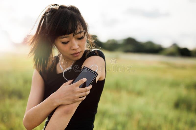 Θηλυκό ικανότητας που ελέγχει την απόδοσή της στο smartphone στοκ φωτογραφίες