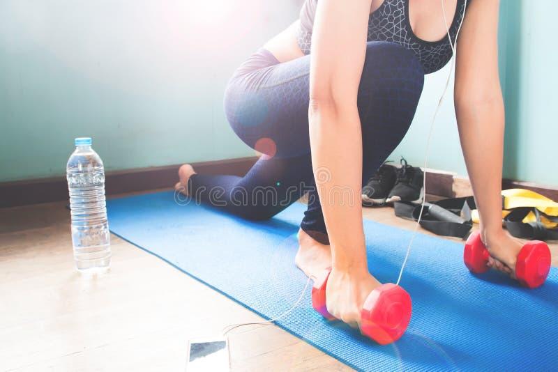 Θηλυκό ικανότητας που τεντώνει το σώμα της στο χαλί γιόγκας, Workout και τον υγιή τρόπο ζωής στοκ φωτογραφίες