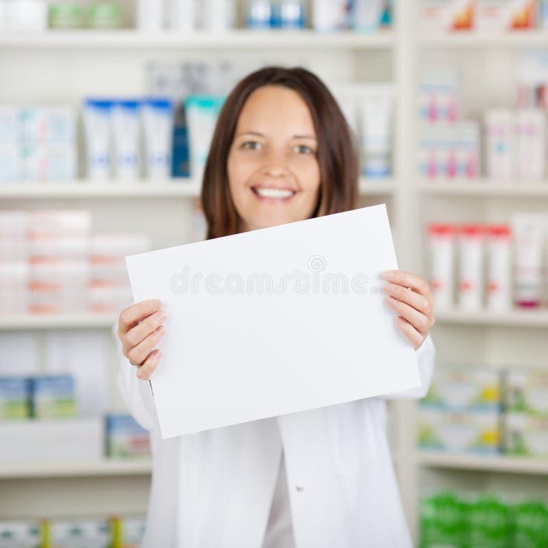 Θηλυκό κενό έγγραφο εκμετάλλευσης φαρμακοποιών στο φαρμακείο στοκ εικόνα με δικαίωμα ελεύθερης χρήσης