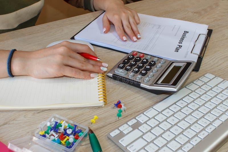 Θηλυκό με το επιχειρηματικό σχέδιο, τον υπολογιστή και τη μάνδρα στον πίνακα Εργασία γυναικών στην αρχή, καθμένος στο γραφείο, πο στοκ εικόνα