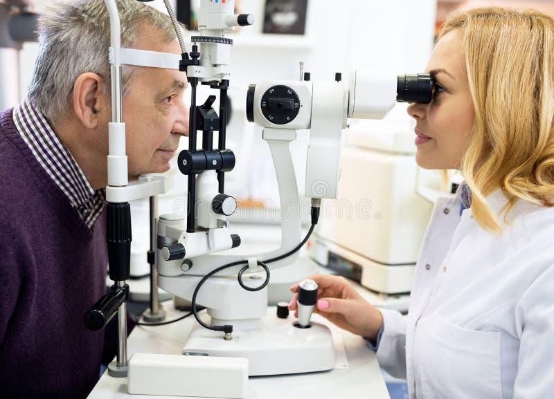 Θηλυκό οφθαλμικό άτομο ματιών ελέγχου γιατρών στην κλινική ματιών στοκ φωτογραφία με δικαίωμα ελεύθερης χρήσης