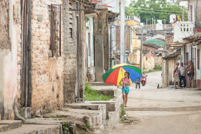 Θηλυκό παιδί με την πολύχρωμη ομπρέλα που περπατά στις οδούς του Τρινιδάδ Κούβα στοκ φωτογραφία με δικαίωμα ελεύθερης χρήσης