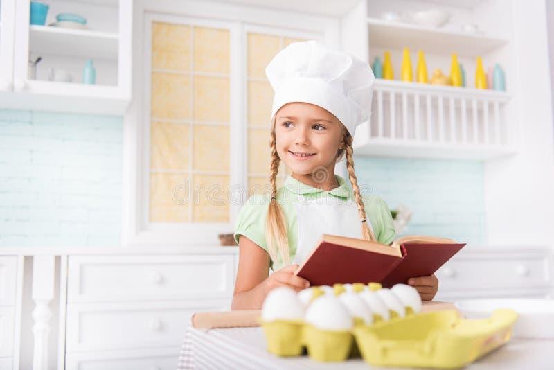 Θηλυκό παιδί Dreamful που προετοιμάζεται για το μαγείρεμα στοκ εικόνα με δικαίωμα ελεύθερης χρήσης