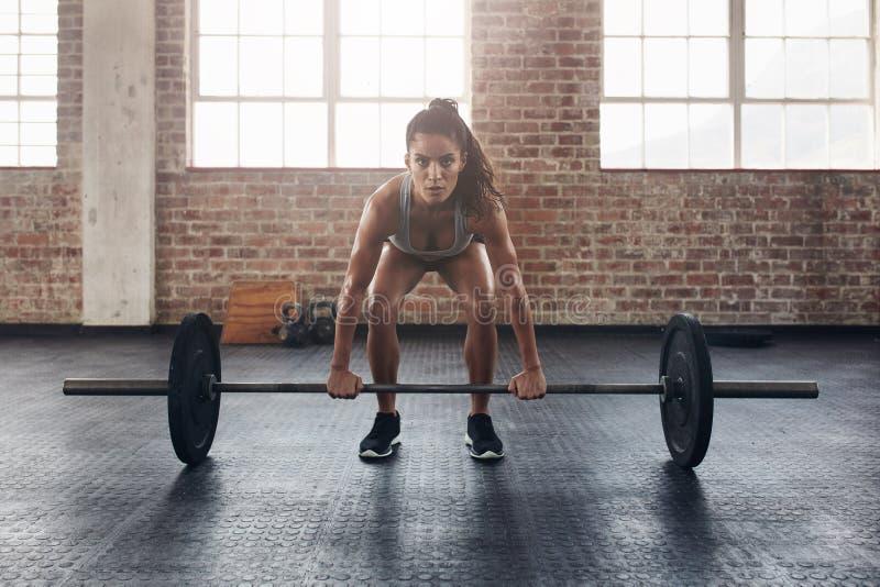 Θηλυκό που εκτελεί deadlift την άσκηση με το φραγμό βάρους στοκ εικόνα με δικαίωμα ελεύθερης χρήσης