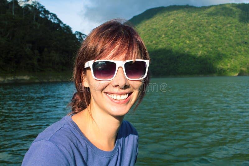 Θηλυκό πρόσωπο με το χαμόγελο στο υπόβαθρο της δασικής λίμνης Κορίτσι στο ταξίδι λιμνών ή ποταμοπλοίων στοκ εικόνα με δικαίωμα ελεύθερης χρήσης