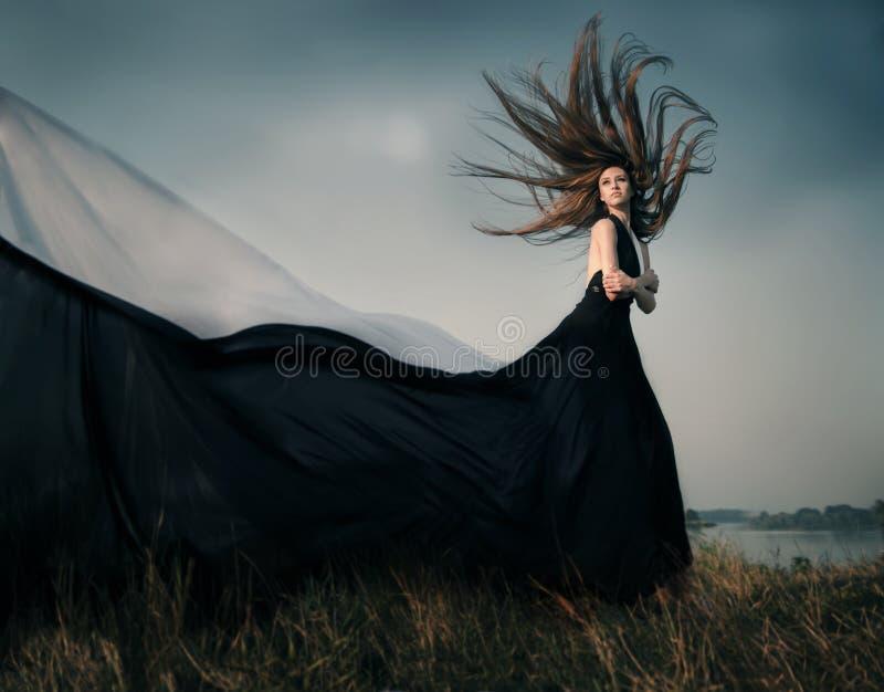 Θηλυκό πρότυπο μόδας με τη μακριά φυσώντας τρίχα υπαίθρια στοκ εικόνα