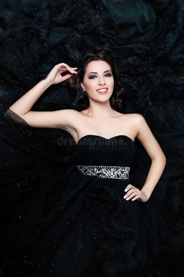 Θηλυκό πρότυπο που βρίσκεται στο μαύρο προκλητικό φόρεμα στοκ εικόνα