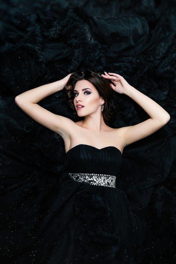 Θηλυκό πρότυπο που βρίσκεται στο μαύρο προκλητικό φόρεμα στοκ εικόνες