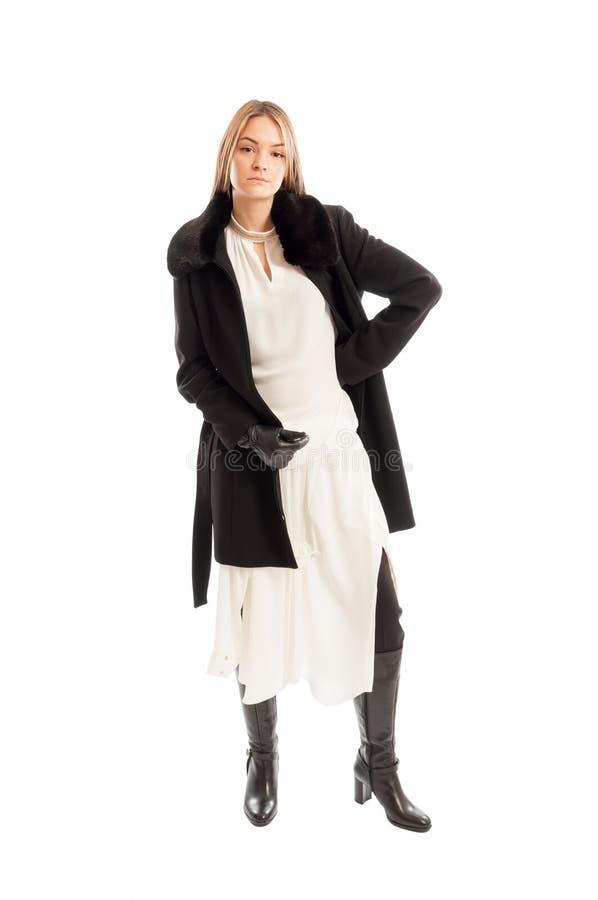 Θηλυκό πρότυπο που φορά το μαύρο παλτό μαλλιού στο άσπρο φόρεμα στοκ φωτογραφία με δικαίωμα ελεύθερης χρήσης