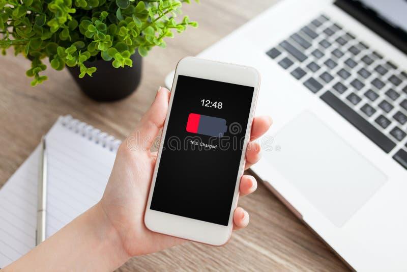 Θηλυκό χέρι που κρατά το άσπρο τηλέφωνο με τη χαμηλά φορτισμένη οθόνη μπαταριών στοκ εικόνα