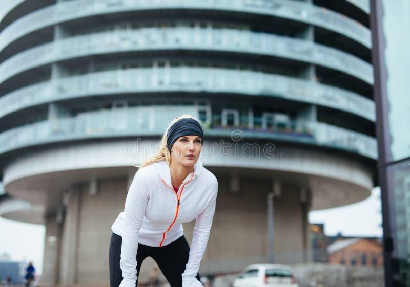 Θηλυκό jogger που παίρνει ένα σπάσιμο στοκ φωτογραφία