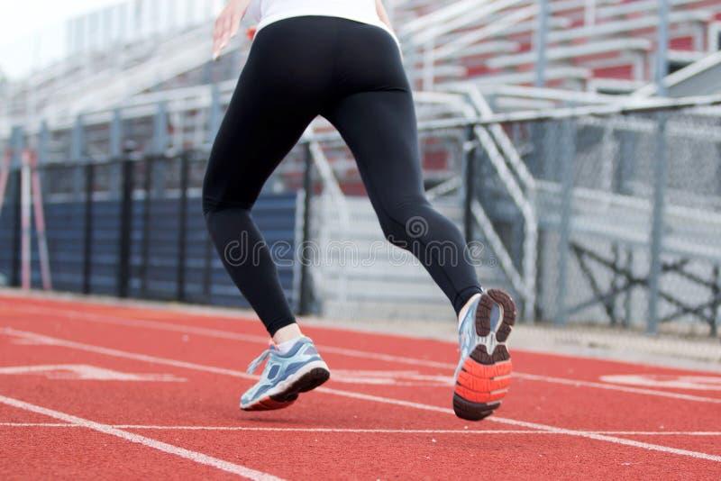 Θηλυκό sprinter που απογειώνεται κάτω από τη διαδρομή στοκ εικόνες