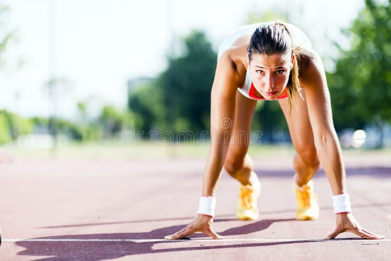Θηλυκό sprinter που παίρνει έτοιμο για το τρέξιμο στοκ φωτογραφίες με δικαίωμα ελεύθερης χρήσης