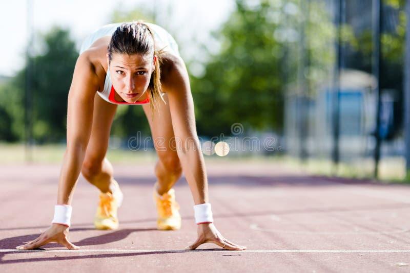 Θηλυκό sprinter που παίρνει έτοιμο για το τρέξιμο στοκ εικόνες