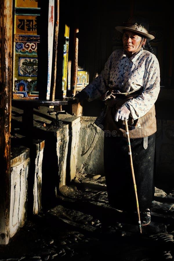 θιβετιανή γυναίκα προσκυνητών που περπατά γύρω από το ναό με τη στροφή των ροδών προσευχής ως μέρος μιας διαδρομής προσκυνήματος στοκ εικόνα