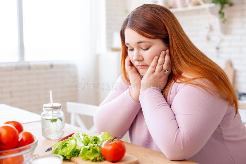Θλιβερή λυπημένη παχουλή γυναίκα που εξετάζει τα λαχανικά στοκ φωτογραφίες με δικαίωμα ελεύθερης χρήσης