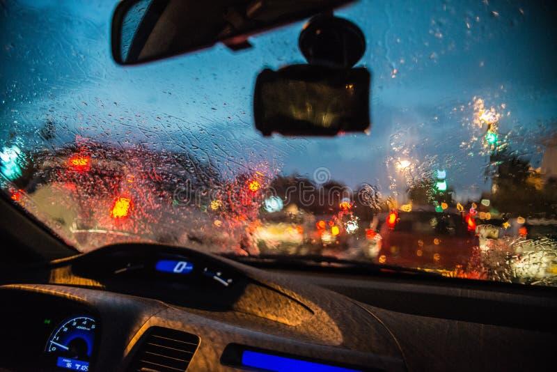 Θολωμένες περίληψη πτώσεις βροχής στο παράθυρο γυαλιού αυτοκινήτων με το υπόβαθρο φωτεινών σηματοδοτών bokeh στοκ φωτογραφία με δικαίωμα ελεύθερης χρήσης
