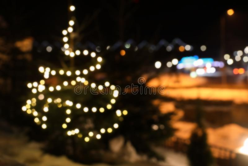 Θολωμένη άποψη του δέντρου κωνοφόρων με τα φω'τα Χριστουγέννων πυράκτωσης στην οδό, διάστημα για το κείμενο στοκ φωτογραφία
