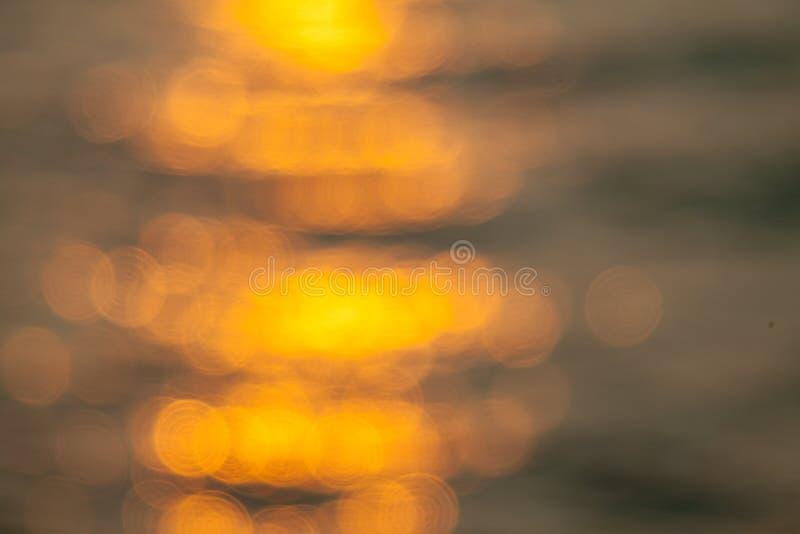 Θολωμένη αντανάκλαση θάλασσας κυμάτων στο φως του ήλιου bokeh υπόβαθρο στοκ φωτογραφία