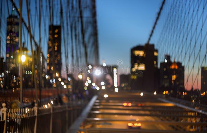 Θολωμένη γέφυρα του Μπρούκλιν αστικής κυκλοφορίας στο λυκόφως στη σκηνή υποβάθρου πόλεων της Νέας Υόρκης τη νύχτα στοκ εικόνα