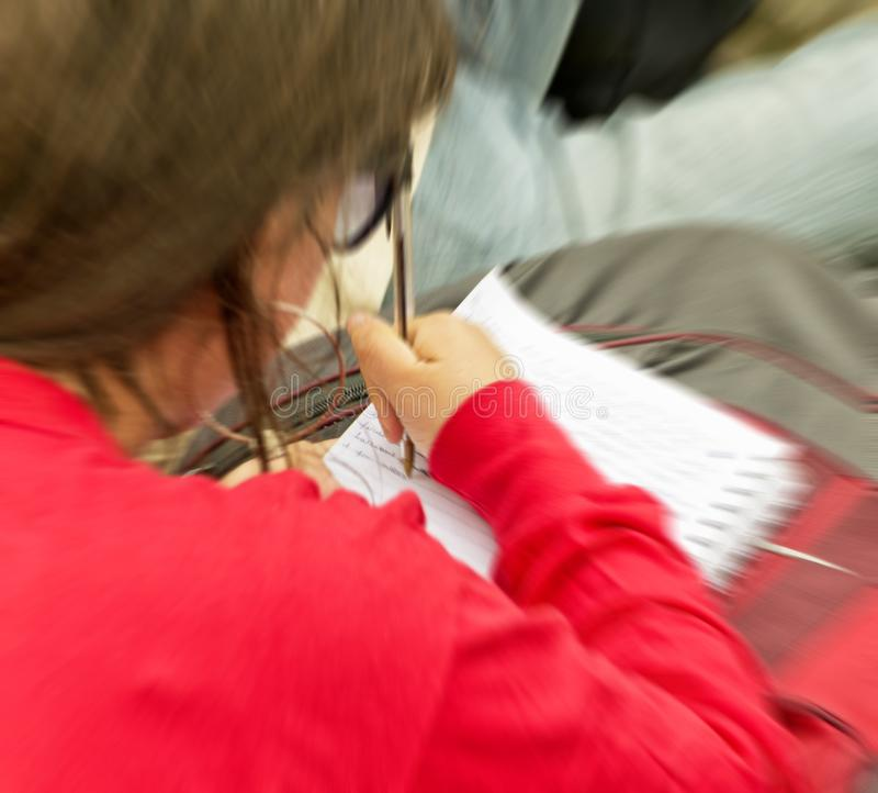 Θολωμένη εικόνα ενός κοριτσιού που παίρνει τις σημειώσεις κατά τη διάρκεια του μαθήματος για την εκπαιδευτική και σχολική έννοια στοκ φωτογραφία