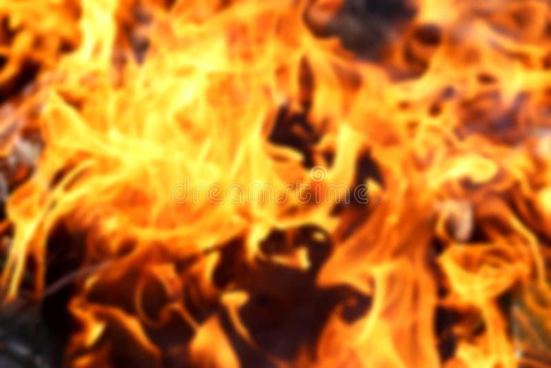 Θολωμένη σύσταση των φωτεινών πορτοκαλιών φλογών πυρκαγιάς που καίνε το ξύλο στο έκκεντρο στοκ εικόνα