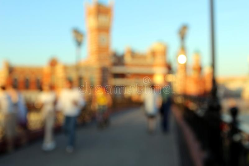 Θολωμένη φωτογραφία των ανθρώπων που περπατούν κατά μήκος του δρόμου πέρα από τη γέφυρα το βράδυ στο ηλιοβασίλεμα στοκ εικόνα