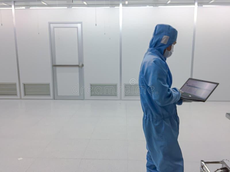 Θολωμένος μηχανικός μέσα στην καθαρή κατηγορία 1000 δωματίων με την πόρτα έκτακτης ανάγκης στο εργοστάσιο, κενό δωμάτιο στοκ εικόνα