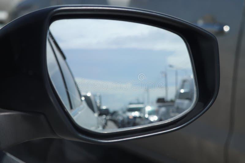 Θολωμένος της κυκλοφοριακής συμφόρησης στον καθρέφτη φτερών του αυτοκινήτου στο δρόμο στοκ εικόνα