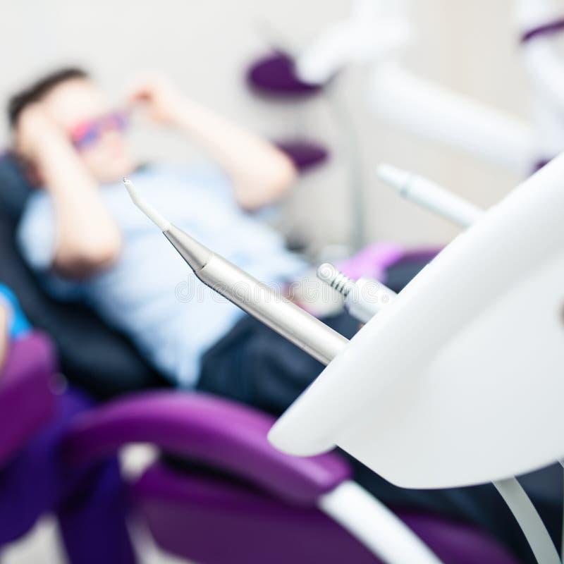 Θολωμένο οδοντικό γραφείο Τα εργαλεία είναι στο πρώτο πλάνο Ένα αγόρι με τα προστατευτικά δίοπτρα στην οδοντική καρέκλα στοκ εικόνα