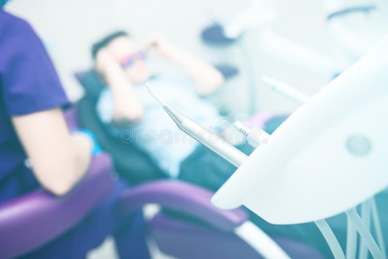 Θολωμένο οδοντικό γραφείο Τα εργαλεία είναι στο πρώτο πλάνο Ένα αγόρι με τα προστατευτικά δίοπτρα στην οδοντική καρέκλα στοκ εικόνες