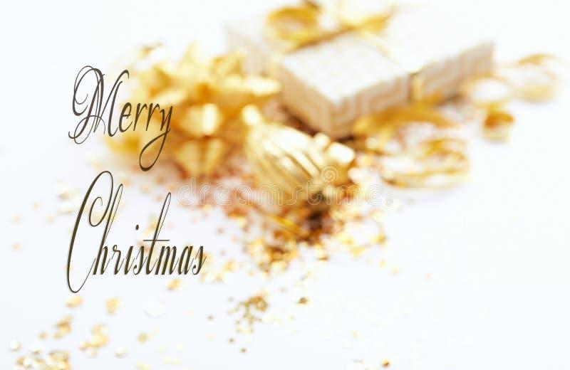 Θολωμένο υπόβαθρο Χριστουγέννων Χρυσές διακοσμήσεις και ένα κιβώτιο δώρων Άσπρη ανασκόπηση στοκ εικόνες