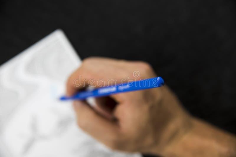 Θολωμένο χέρι που χειρίζεται έναν μπλε χρωματισμό μολυβιών στοκ εικόνες με δικαίωμα ελεύθερης χρήσης