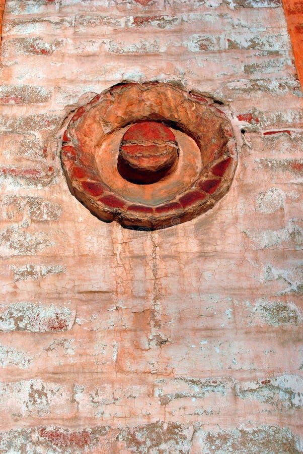 Θρυμματιμένος παλαιός τουβλότοιχος κόκκινου χρώματος με τη διακόσμηση στη μορφή του κύκλου στοκ εικόνες