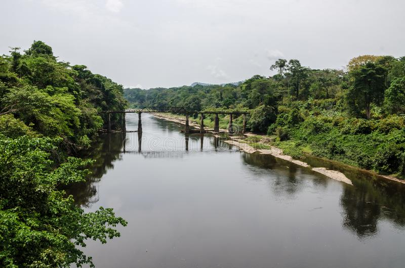Θρυμματιμένος σίδηρος και συγκεκριμένη γέφυρα που διασχίζουν τον ποταμό Munaya στο τροπικό δάσος του Καμερούν, Αφρική στοκ φωτογραφία