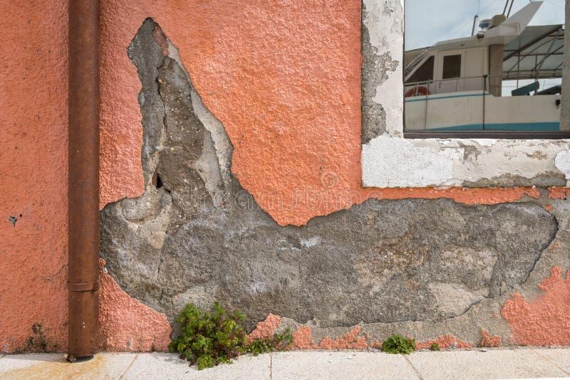 Θρυμματισμένο ασβεστοκονίαμα ενός πορτοκαλιού τοίχου, αντανάκλαση μιας βάρκας στο παράθυρο στοκ φωτογραφία με δικαίωμα ελεύθερης χρήσης