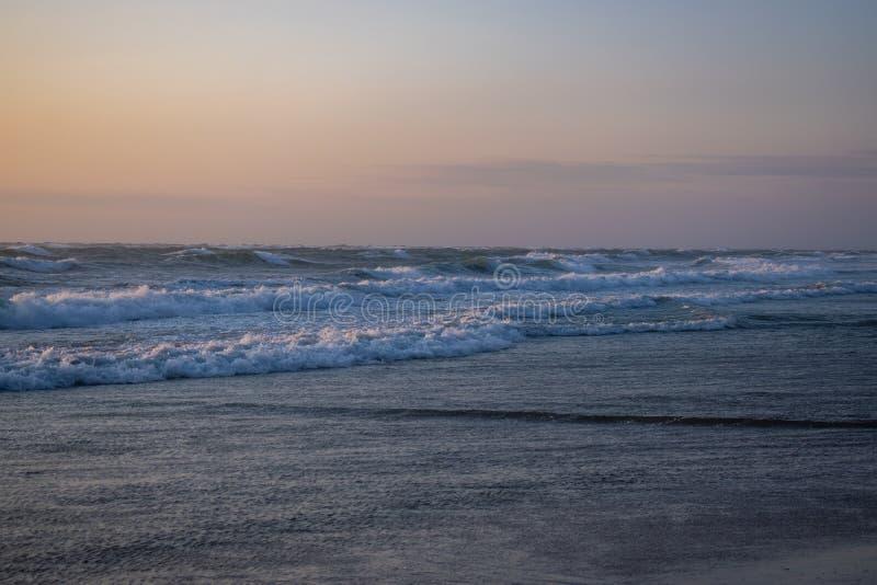 Θυελλώδες ηλιοβασίλεμα στην παραλία Løkken Δανία Βόρεια περιοχή Ζωηρόχρωμος και ευμετάβλητος ουρανός Κύματα από τα ses στοκ φωτογραφίες