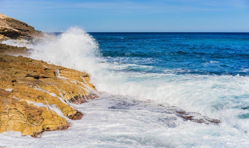 Θυελλώδες seascape με τα ισχυρά foamy κύματα του ωκεάνιου ραντίσματος νερού ενάντια στη δύσκολη ακτή στοκ εικόνα με δικαίωμα ελεύθερης χρήσης